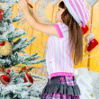 Little girl is decorating christmas tree — Stock Photo