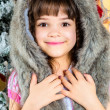 Cute little happy girl posing in a fur hat. — Stockfoto