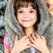 Stockfoto: Cute little happy girl posing in a fur hat.