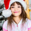 Happy little girl in santa's hat in front of christmas tree — Stock Photo