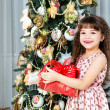 Happy little girl with christmas present smiling — Stock Photo