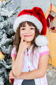 Happy little girl in santa's hat in front of christmas tree — Stok fotoğraf
