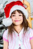 Happy little girl in santa's hat in front of christmas tree — Foto Stock