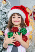 Little girl in Santa hat holding Christmas decoration in hands — Stock Photo