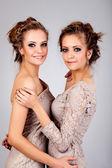 Dvě holky dvojčata, izolovaných na šedém pozadí — Stock fotografie