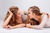 две девушки близнецы, изолированные на сером фоне — Стоковое фото