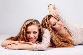 Bliźniaki dwie dziewczyny, na białym tle na szarym tle — Zdjęcie stockowe