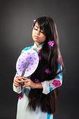 Schöne asiatische frau trägt ein nationales kleid hält ein fan — Stockfoto