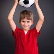 Boy holding a soccer ball over his head — Stock Photo