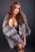 Attractive woman in fur coat and bra — Stock Photo