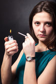 Beautiful young woman is smoking cigarette on black background — Stock Photo