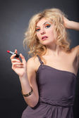 Blond woman holding a red lipstick — Stockfoto