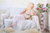 Blonde woman in a white dress on the couch — Stock Photo