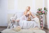 Blonde Frau in einem weißen Kleid mit einem Hund — Stockfoto