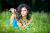 Jonge vrouwelijke ontspannen liggen op haar buik in het gras — Stockfoto