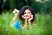 Young female relax lying on her stomach in the grass — Stock Photo