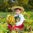 Smiling boy holding  big yellow pumpkin in hands — Stock Photo #42301699