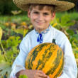 Smiling boy holding  big yellow pumpkin in hands — Stock Photo #42301795