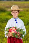 Happy farmer boy håller ekologiska äpplen på hösten trädgård — Stockfoto