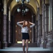 Beautiful young woman standing near old columns — Stock Photo #43004297