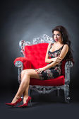 Young woman in a red chair. Retro style. — Foto Stock