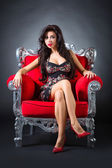 Young woman in a red chair. Retro style. — Stockfoto