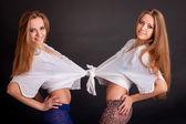 Two beautiful girls twins, on black — Stok fotoğraf