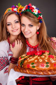 Young women in ukrainian clothes, with garland and round loaf — Stock Photo