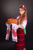 Young woman in ukrainian clothes, with garland and round loaf — Stock Photo