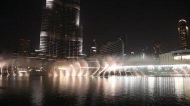 Fountain near Burj Khalifa illuminated by the city at night — Stock Video