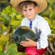 Smiling boy holding  big yellow pumpkin in hands — Stock Photo #48910661