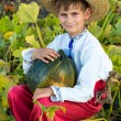 Smiling boy holding  big yellow pumpkin in hands — Stock Photo #48910769