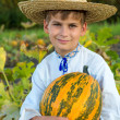 Smiling boy holding  big yellow pumpkin in hands — Stock Photo #48910889