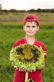 Mutlu çocuk tutun ayçiçeği bahçe içinde — Stok fotoğraf