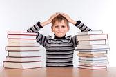 Schooljongen en een hoop van boeken — Stockfoto