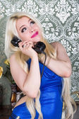 Woman in blue dress talking on the phone — ストック写真
