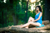 Beautiful Young Woman sitting on log — Photo