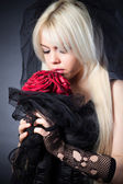 Black widow in grief with flowers — Stock Photo