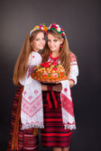 Women in ukrainian clothes with round loaf — Stock Photo
