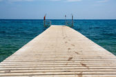 Pier with a wet footprints and a shower — Stock Photo
