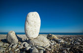 Big white pebble balancing on a beach — Stock Photo