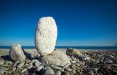 Big white pebble balancing on a beach — Stock Photo