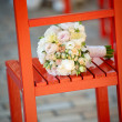 Wedding bouquet on red chair — Stock Photo #29154485