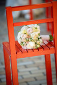 Wedding bouquet on a red chair — Stock Photo