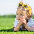 Little girl with sun glasses on a grass — Stock Photo #41396419