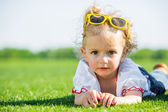 Little girl with sun glasses on a grass — Стоковое фото