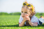 Little girl with sun glasses on a grass — Foto Stock