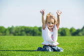 Little happy girl on a grass — Stok fotoğraf