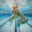 Boy swimming under water - Stock Photo
