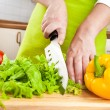 Foto Stock: Woman's hands cutting vegetables